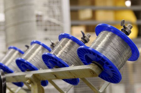 Spools of wire on a stitching machine in a printing plant Imagens