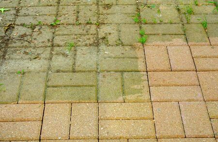 Grimy and clean sections of patio showing amazing results of power washing