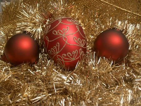 Three red Christmas ornaments nested on gold tinsel