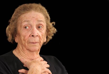Elderly woman holding hands in a gesture of apprehension