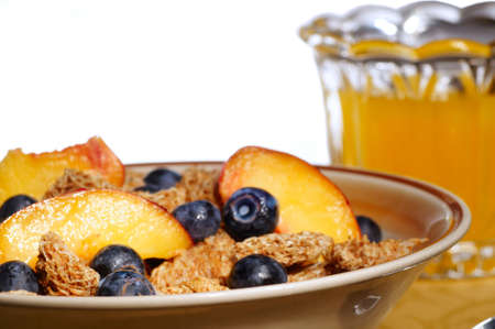 A healthy breakfast of cereal with blueberries and nectarine slices and orange juice against a white backdrop