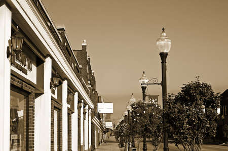 Storefronts, sidewalks, and lamp posts in small-town America, monochrome, sepia