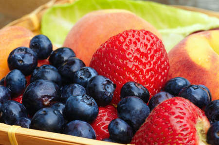 Luscious blueberries, strawberries, and peaches in a shallow basket