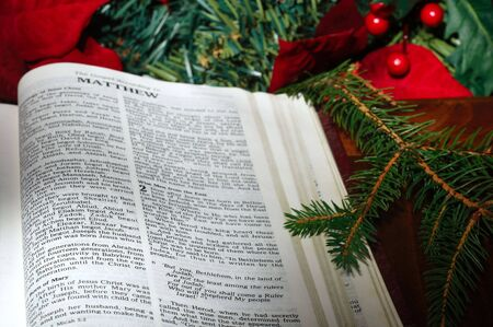 Bible open to the Christmas narrative in Matthew with poinsettias and evergreens