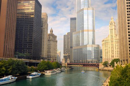 Boats on the Chicago River surrounded by towering skyscrapers 写真素材