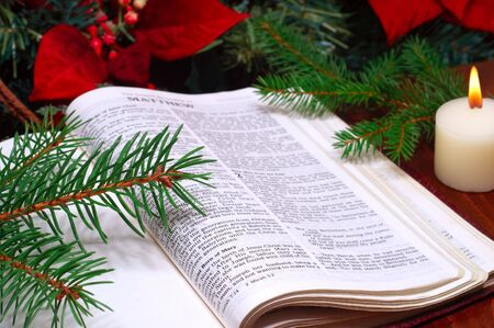 Bible open to the Christmas passage of Matthew 2 with candle, poinsettia, and evergreen sprigs Foto de archivo