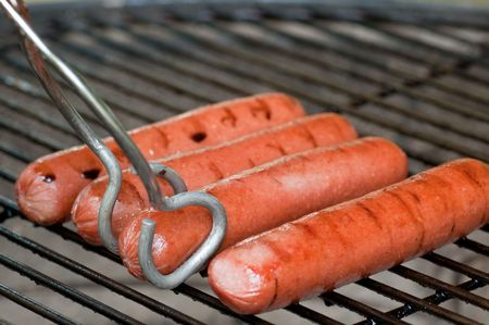 Four hot dogs on a charcoal grill with tongs about to turn one