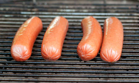 Four hot dogs just beginning to cook on a charcoal grill Stock Photo