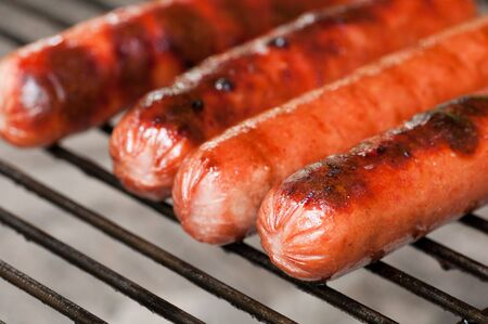Four hot dogs getting nicely done on a charcoal grill Banque d'images