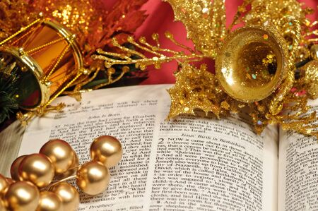 Bible open to the Christmas passage of Luke 2 decorated with drum, berries, and bell