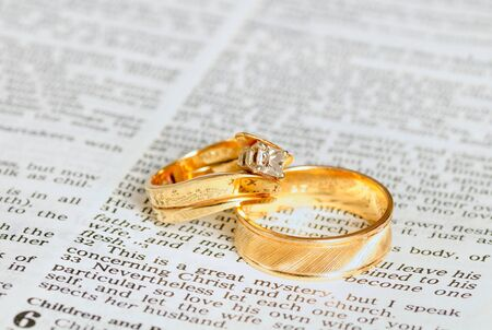Two wedding rings on top of the marriage passage from Ephesians in the Bible