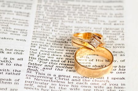 Two gold wedding rings rest on the marriage passage from Ephesians 5 in the Bible 版權商用圖片