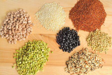 Matrix van korrels - pinto bonen, quinoa, linzen, rijst, zwarte bonen en erwten - op een snijplank Stockfoto