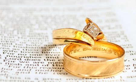 Two gold wedding rings rest on the marriage passage from Ephesians 5 in the Bible Foto de archivo