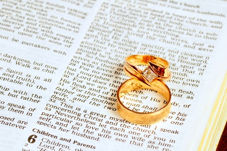 Two gold wedding rings rest atop the marriage passage from Ephesians 5 in the Bible