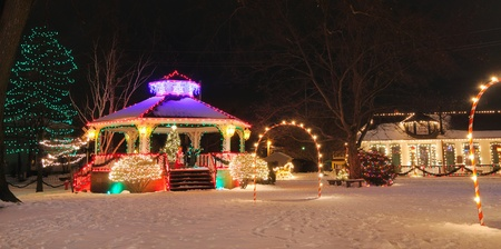 A festively lit small-town gazebo and train depot at Christmas