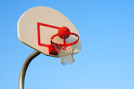 A basketball shot about to drop through the net
