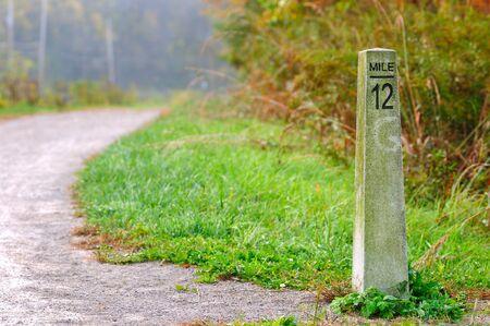 Marqueur de mile en pierre sur un sentier de randonnée / jogging Banque d'images - 11977460