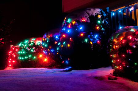 Outdoor Christmas lights casting a colorful glow on the snow