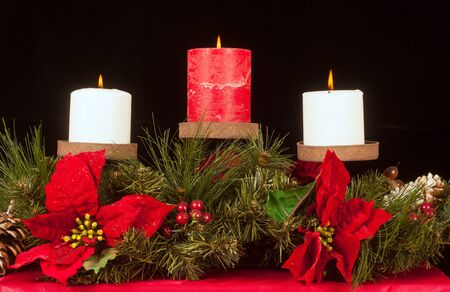 크리스마스 촛불의 트리오는 상록수와 포인세티아의 침대에 장착