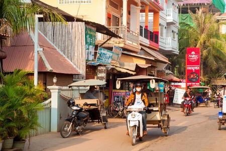Siem Reap, Cambodja - 17 februari 2014 Tuk tuk chauffeurs veerboot ruiters of wacht voor het bedrijfsleven op een drukke ochtend in deze Cambodjaanse stad in de buurt van de belangrijkste toeristische attractie van Angkor Wat Redactioneel