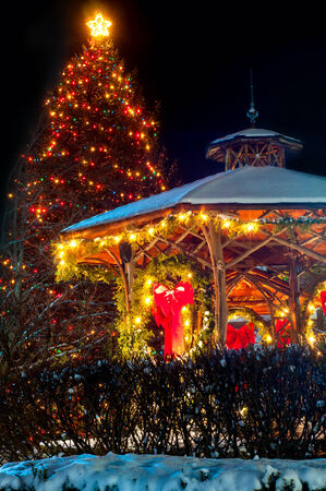a village christmas tree and gazebo are festively lit up for the holidays stock photo