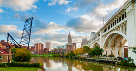 The Cuyahoga River bends past downtown Cleveland by the Veterans Memorial Bridge with old lift bridge at left 報道画像