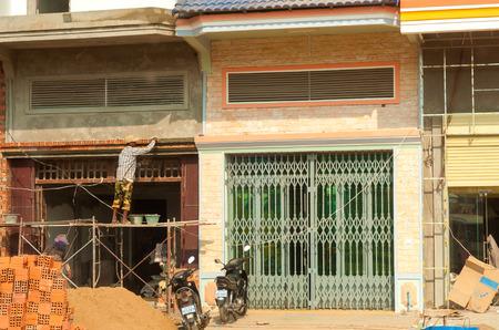 Phnom Penh, Cambodja - 27 februari 2014: Een metselaar legt de laatste hand aan de renovatie van gebouwen in deze drukke en economisch groeiende Aziatische hoofdstad.