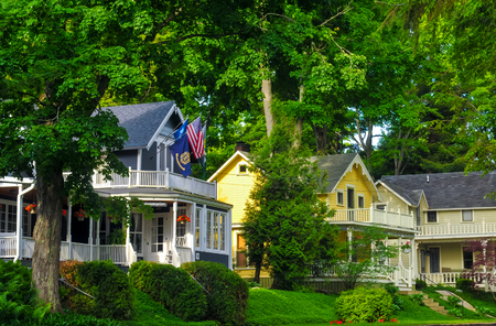 BAY VIEW, MI - JUNE 26, 2014: Quaint old homes, many of them providing tourist lodgings, line the shady streets of this one-time Methodist retreat center next to Petoskey on Lake Michigan. Imagens - 38361121
