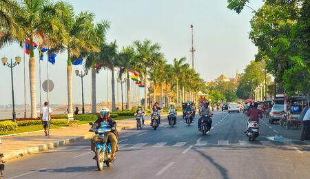 PHNOM PENH CAMBODJA 1 maart 2014: verkeer beweegt langs Preah Sisowath Quay langs de Tonle Sap rivier met zijn parade van palmen en internationale vlaggen. Gebouwen van het Koninklijk Paleis Park zijn zichtbaar in de verte. Redactioneel
