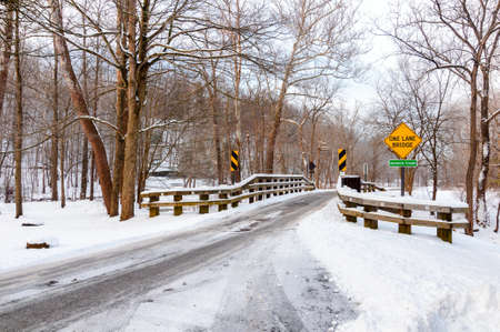 Snow covers a one-lane bridge over a creek in an Ohio park Reklamní fotografie