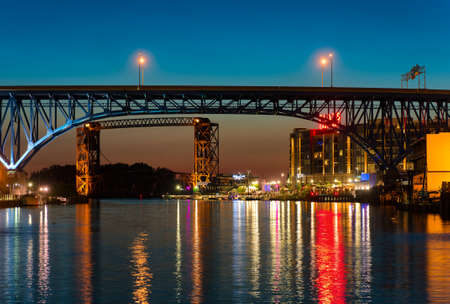 CLEVELAND, OH - JUNE 17 2016: The east bank of the Cuyahoga, under highway and railroad bridges, glows with the lights of a new vibrant entertainment district.