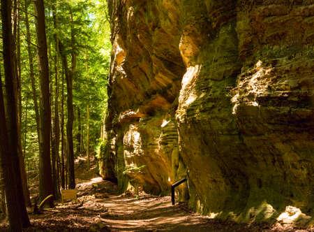 오하이오 주에있는 Whispering Cave의 흔적 Hocking Hills State Park는 우뚝 솟은 절벽 아래에서 달립니다.
