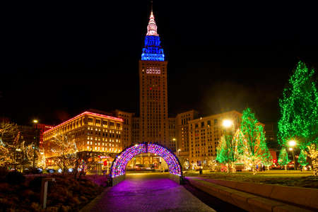 CLEVELAND, OH - DECEMBER 30, 2016: Cleveland's Terminal Tower, lit up for Christmas, stands over brightly lit holiday displays on Public Square.
