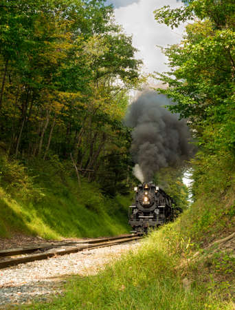 PENINSULA, OH - SEPTEMBER 17, 2917: The NKP-765, one of the largest steam locomotives still in existence, approaches with a full billow of smoke from a narrow pass through woods south of Cleveland.