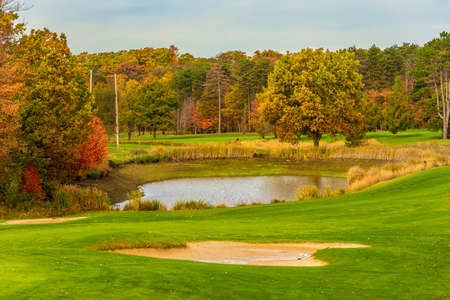 A golf course water trap and fairways amid autumn colors Stock Photo