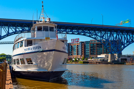 CLEVLEAND, OH - MAY 25, 2018: The Nautica Queen, a popular ship for dinner cruises on the Cuyaghoa River and Lake Erie, rests at her dock before the Main Avenue Bridge and Flats East Bank entertainment area. Archivio Fotografico - 108551650