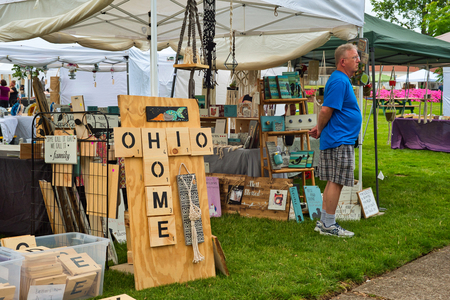 TWINSBURG, OH - JUNE 9, 2018: A visitors waits outside the Ohio Home craft booth at A Taste of Twinsburg, an outdoor culinary and arts festival held one Saturday in summer on the town square.