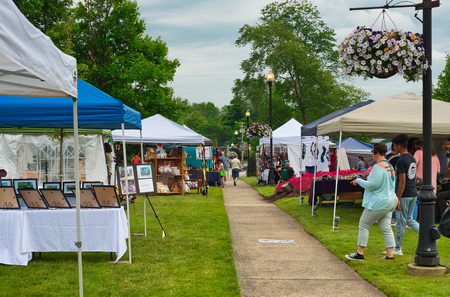 TWINSBURG, OH - JUNE 9, 2018: Visitors stroll among vendor booths for A Taste of Twinsburg, an outdoor culinary and arts festival held one Saturday in summer on the town square.