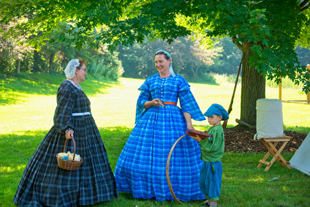 TWINSBURG, OH - JUNE 30, 2018: Two women and a young child in period dress portray Civil War era women and civilian life during an all-day history event at the Twinsburg Public Library. Sajtókép