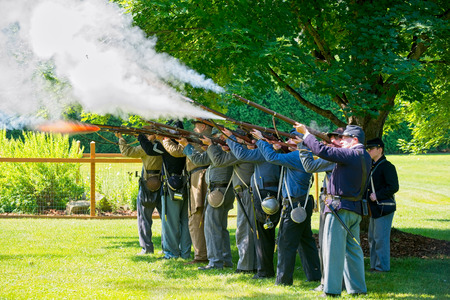 TWINSBURG, OH - JUNE 30, 2018: Civil War reenactors, here representing both Union and Confederate soldiers demonstrate in-line rifle firing during an all-day history event at the Twinsburg Public Library. Editorial