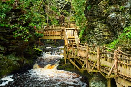 Wooden walkway along Little Bushkill Creek above the main falls at Bushkill Falls Stock Photo