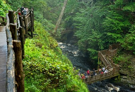 BUSHKILL FALLS, PA, USA - SEPTEMBER 3, 2018: Visitors take in the scenic sights from the walkways and bridges above Bushkill Creek below the main falls and above the lower falls in the distance.