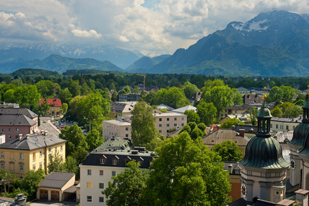 VIew of the Alps at Salzburg, Austria, with the Untersberg at right, from a high point behind the Nonnberg Abbey looking south, with the cupolas or Sankt Erhard Catholic church at lower right