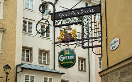 SALZBURG, AUSTRIA - MAY 26, 2019: The ornate sign for the Gablerbräu restaurant hangs above the Stefan-Zweig Platz in a charming section of this beautiful city's old town.