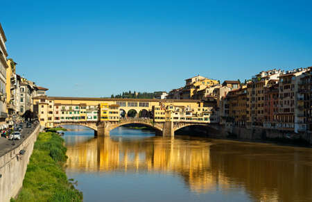 The Ponte Vecchio in Florence, Italy, casts late-afternoon reflections in the Arno River on a bright spring day.