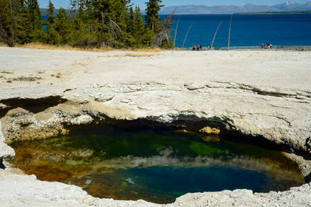 A colorful pool in the West Thumb Geyser Basin at Yellowstone National Park, with Yellowstone Lake in the background