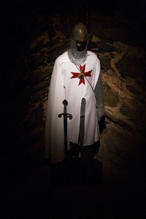 Costume of a templar with sword in the dark with stone background