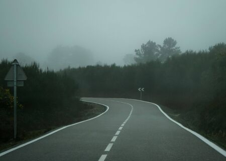 View of a road with a curve in the background and left arrow sign on a foggy day Stok Fotoğraf