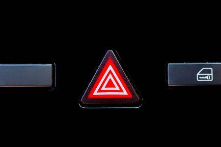 Warning button illuminated on the dashboard of a car